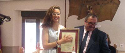 Rocío Herrero recibe el tradicional pergamino de reconocimiento de manos del presidente del Centro Católico de Obreros.